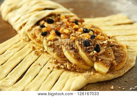 Strudel with apples, walnut and raisins in raw dough on wooden table