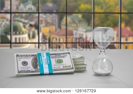 Desk with hourglass and dollars. Bundle of cash and hourglass. Clerk's table at daytime. Real estate at low prices.