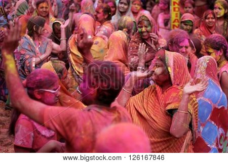 HYDERABAD,INDIA-MARCH 24: Hindu men and women celebrating Holi festival smearing colored powder a tradition on March 24,2016 in Hyderabad,India