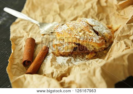 Slice of strudel with apples, walnut and raisins on parchment