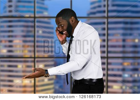Smiling black man with phone. Happy businessman on skyscraper background. His theory is finally proved. Chief's happy evening.