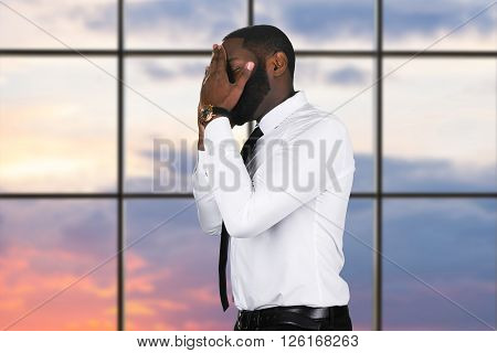 Upset black guy with cellphone. Businessman's facepalm on sunset background. Such a shame. Running out of luck.