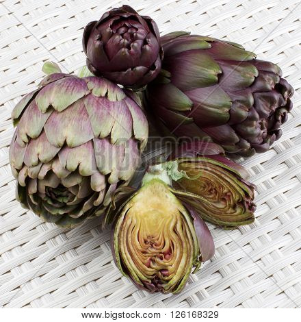 Perfect Raw Artichokes Full Body and Halves closeup on Wicker background
