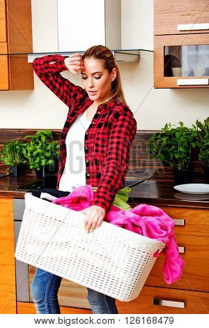Tired young woman carrying laundry basket in kitchen