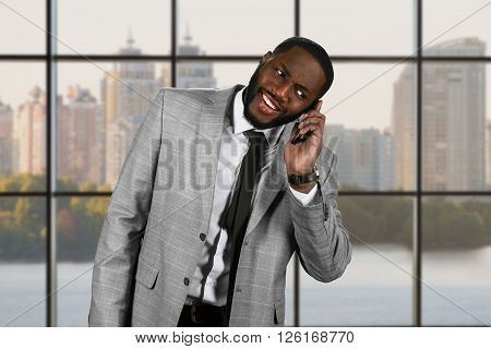 Surprised afro man holding phone. Executive in suit at daytime. Motivation on workplace. Find ways to convey happiness.