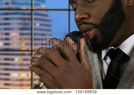Afro singer with eyes closed. Bearded vocalist on evening background. Concentration and skill. Gentleman's  impressive baritone.