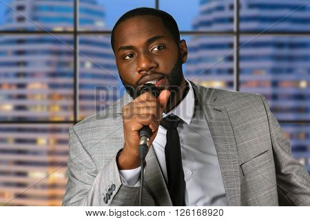 Black man speaks into microphone. Young speaker on evening background. Advice and motivation. Famous expert at business seminar.