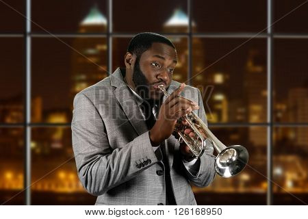 Expressive afro guy playing trumpet. Young trumpeter in big city. Blues performer at his best. Wonderful rhythmic music.