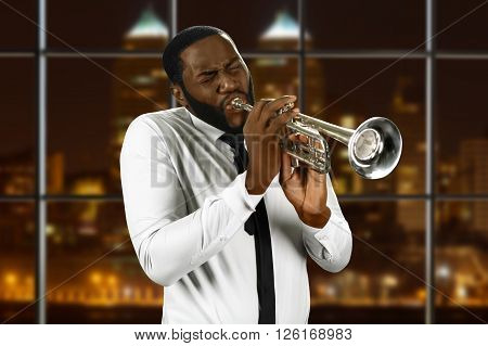 Man in shirt playing trumpet. Black trumpeter in night city. Concert for jazz lovers. Live performance of awesome music.