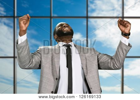 Cheerful afro businessman in jacket. Elated manager on sky background. Indisputable victory for executive. Leader celebrating his success.