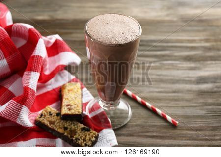 Glass of chocolate milkshake and cookies on wooden background