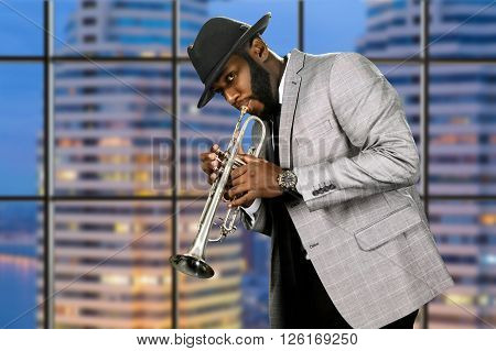 Man in hat playing trumpet. Darkskinned trumpeter on evening background. Live ska performance for fans. Enjoy the purity of music.