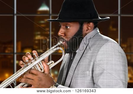 Guy in hat plays trumpet. Afro trumpeter on night background. Young ska musician on tour. Music of big city.
