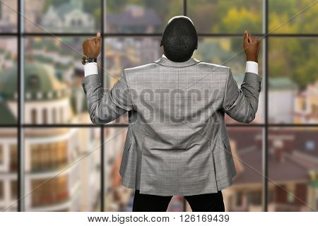 Joyful afro businessman wearing jacket. Back view of elated manager. Huge victory for the company. This world belongs to us.