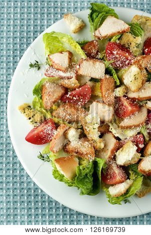 Delicious Caesar Salad with Roasted Chicken Breast Garlic Crouton Romaine Lettuce Cherry Tomatoes and Grated Parmesan Cheese closeup on White Plate. Top View on Napkin