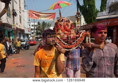 HYDERABAD,INDIA-MARCH 24: Hindu men celebrating Holi festival take idols in the procession singing religious songs as tradition on March 24,2016 in Hyderabad,India