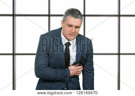 Adult businessman has heart attack. Sick man on white background. Job takes health away. Serious health problems.