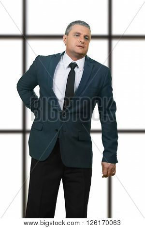 Adult businessman having back pain. Diseased manager on white background. Serious kidney injury. Problem that needs treatment. ** Note: Soft Focus at 100%, best at smaller sizes