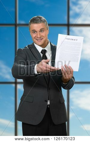 Mature businessman showing contract. Recruiter on blue sky background. Convince and motivate. Read the smallprint.