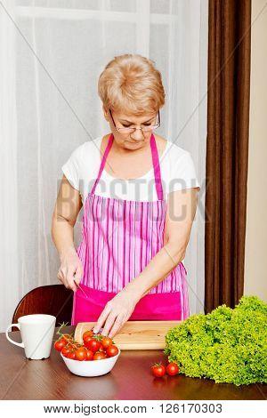 Woman cut red onion on cutting board