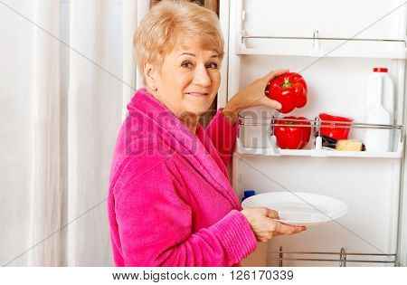Senior woman taking a red paprika from fridge