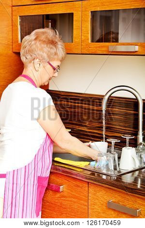 Senior woman washing dishes in the kitchen