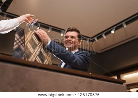 Smiling businessman with bag at counter