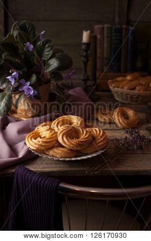 Eclairs or profiterole delicious pastry dessert filled with whipped cream on vintage wooden table background. Provence rustic style.