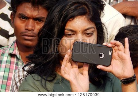HYDERABAD,INDIA-MARCH 27:Indian young adult shoots an event with mobile phone on March 27,2016 in Hyderabad,India.