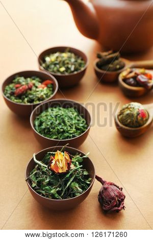Variety of dry tea in bowls with teapot on light brown background, closeup