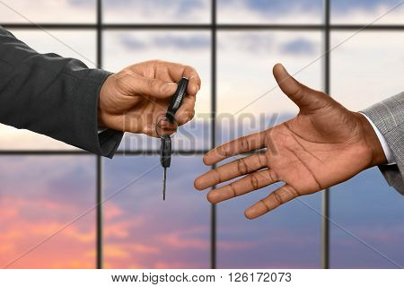 Man's hand passing car key. Car key on sunrise background. Always drive safely. Luxury is not for everyone.