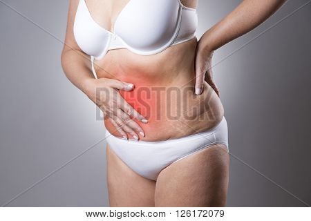 Woman in a white bra and white panties with abdominal pain on a gray background. Studio shot with red dot
