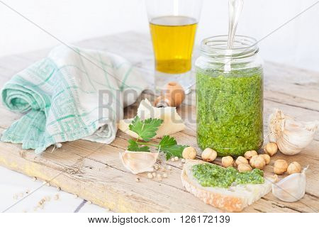 Jar with freshly made parsley pesto sauce besides all the ingredients necessary for its preparation: parsley hazelnuts parmesan cheese extra virgin olive oil and white pepper.