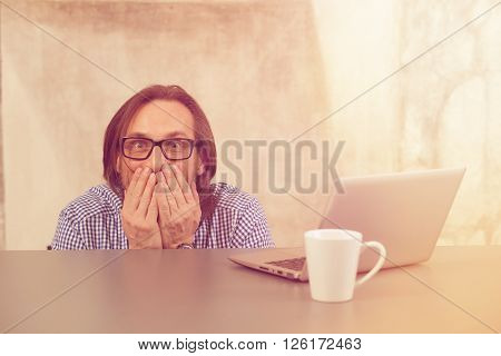 Frightened businessman closing his mouth while sitting under table. Stressed man is afraid of taxmen in office.