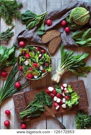 Spring vegetable healthy salad with radish, cucmber, savoy cabbage, parsley, green onion, ramson leek and bread. Healthy vegetarian food.