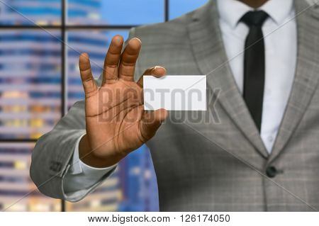 Black businessman shows visit card. Blank white visit card. He's been invited to headquarters. Busy evening of insurance agent.