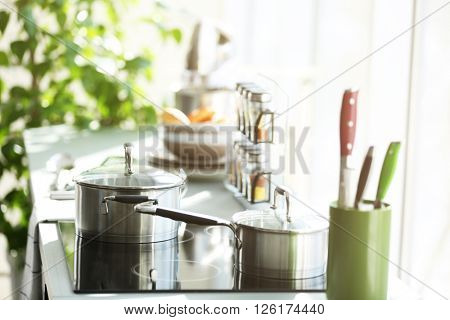 Modern electric stove with utensils in the kitchen beside window, close up