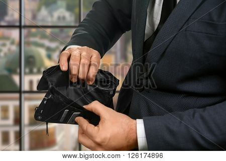 Empty wallet in businessman's hands. Empty wallet on urban background. Waiting for salary. Truly sad situation.