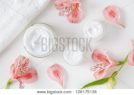 Herbal spa cosmetic cream with pink flowers hygienic skincare lotion product wellness and relaxation makeup mask in glass jar with towel on white background
