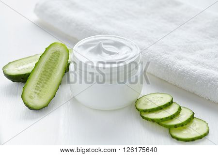 Cucumber cosmetic body cream natural wellness health care hygiene moisture lotion wellness therapy mask in glass jar with towel on white background