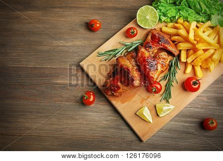 Grilled chicken wings with French fries and garden-stuff on cutting board