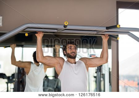 Man doing pull-ups in a gym