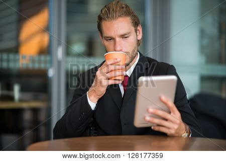 Businessman using his tablet computer while drinking coffee