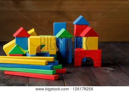 building from wooden colourful childrens blocks on floor