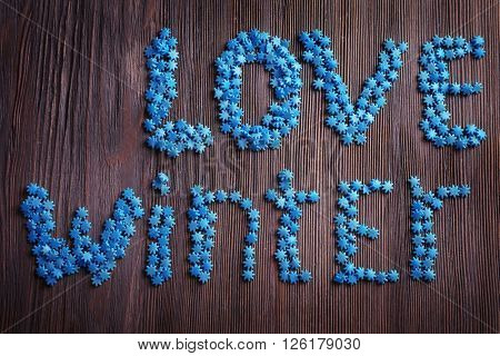 Love winter inscription with candies on wooden background