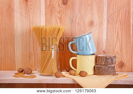 Enamel mugs with spaghetti on wooden background