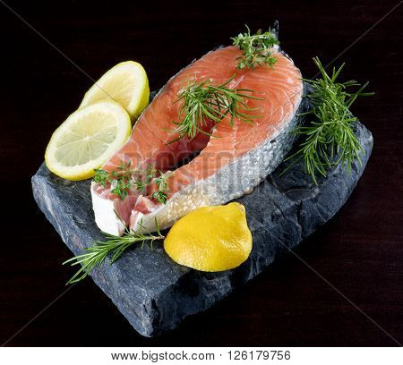Perfect Raw Salmon Steak with Lemon and Rosemary on Shale Stone Board closeup on Dark Wooden background