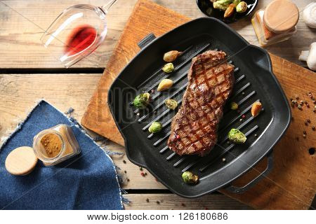 Grilled steak with spice, garlic and Brussels sprouts on grill pan