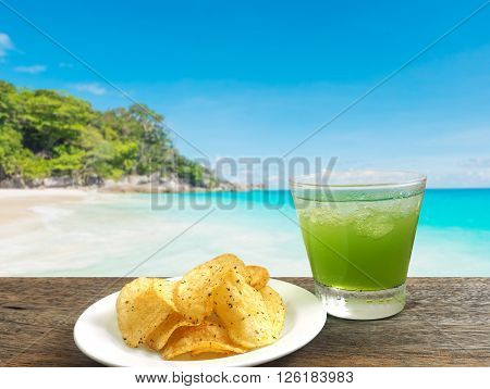 glass of apple juice and potato chips over blurred caribbean beach background