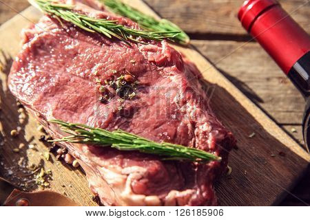 Raw pork steak with bottle of red wine and rosemary wooden background